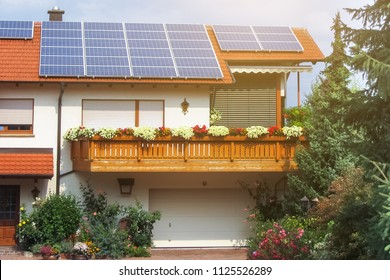 Solar panels on red roof modern eco house.