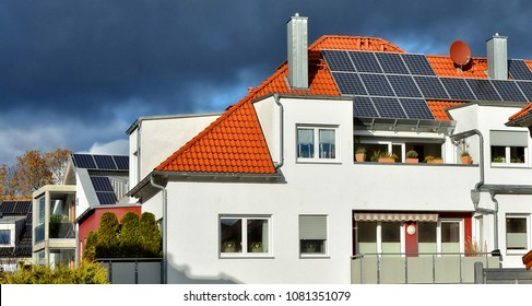 Solar panels on a red tile roof. Modern residential house. Alternative energy. German accommodation. Life in a town.