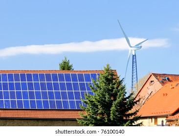 Solar panels on roof of the barn and a windmill behind the farm buildings. Thuringia, Germany