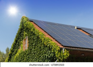 solar panels on a roof with blue sky and sun