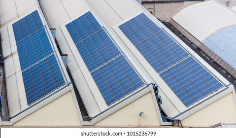 Solar panels on the roof of the building. Sustainable energy usage. Alternative sources of electricity. Advanced technology.