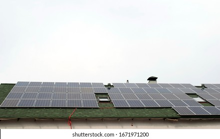 solar panels on the roof of the house in cloudy weather gray sky