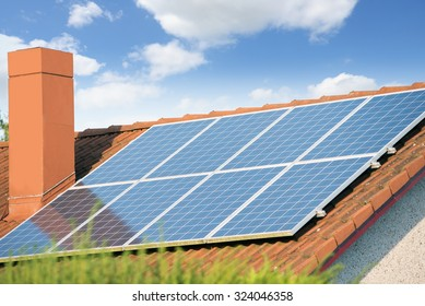 Solar panels on a roof of a house against blue sky