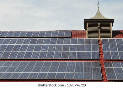 solar panels on roof of old building with wooden turret on top