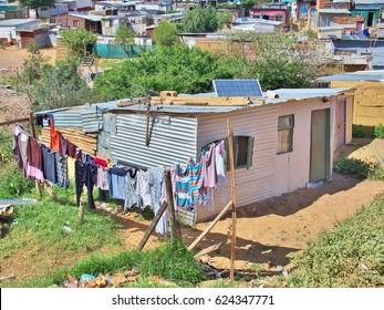 Paneles solares en el techo de la choza del asentamiento informal - Enkanini, en las afueras de Stellenbosch, Cabo Occidental, Sudáfrica. Muchas chozas en Enkanini tienen paneles solares para el acceso a la electricidad.