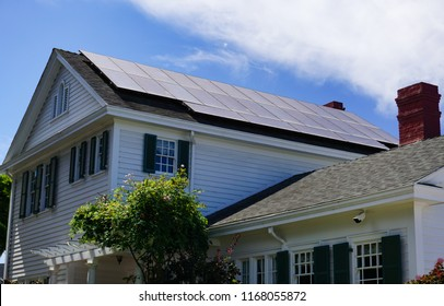 Solar panels on the roof of a traditional Colonial style house beneath a blue summer sky