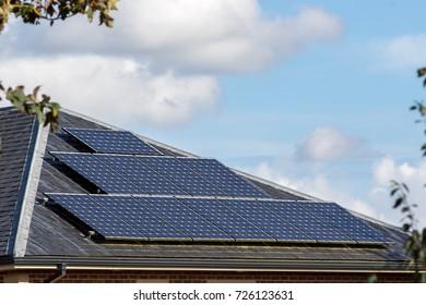 Solar panels on slate tiled roof of modern house, Renewable energy technology installation on domestic building.