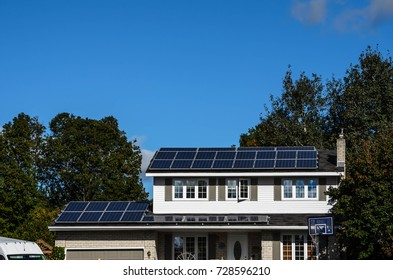 Solar panels on a suburban house rooftop with trees and blue sky background