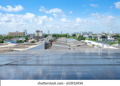 Solar panels on the top roof of a house against the beautiful blue sky and blur of building in the urban city, Bangkok Thailand