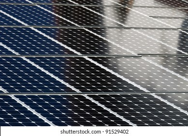 solar panels side by side with the reflection of a building