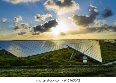 Solar panels at sunrise with cloudy sky in Normandy, France. Solar energy, modern technology of electricity generation, renewable energy sources concept. Environmentally friendly energy production