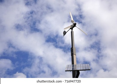 Solar panels wind turbine rotating against sunny blue sky with white clouds. Green energy concept. Copy space