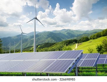 solar panels with wind turbines against mountanis landscape against blue sky with clouds