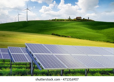 solar panels  and wind turbines against Tuscany mountanis landscape against blue sky with clouds