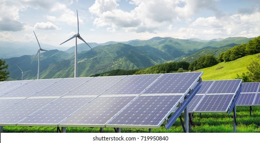 solar panels with wind turbines against mountanis landscape against blue sky with clouds panorama