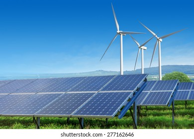 solar panels and wind turbines under blue sky on summer landscape