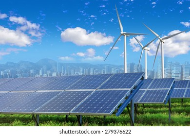 solar panels and wind turbines under blue sky and clouds with city on horizon