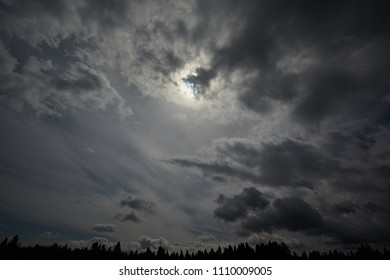 Solar partial eclipse, photos of moon covering the sun with light cloud cover. Gloomy and beautiful clouds