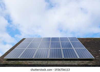 Solar photovoltaic panels on a clay tile roof in England, United Kingdom, with copy space and sky