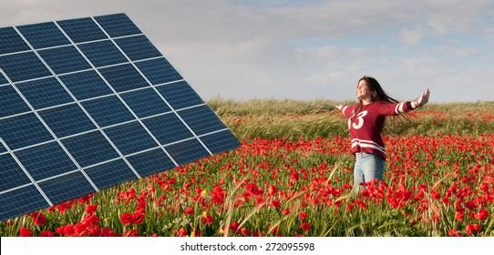 Solar power energy panel on a field with red poppy flowers and a teenage girl jumping happy with joy for saving the environment.  Concept of renewable energy sources.