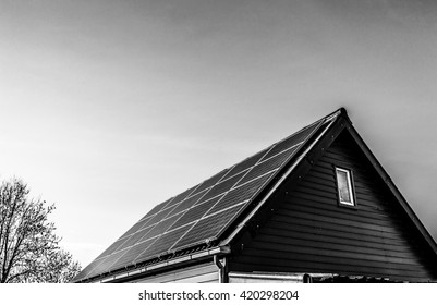 Solar power generation technology on house roof, alternative energy and environment protection ecology. Black-white photo.