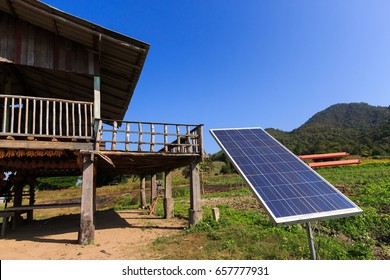 Solar Power Panel with Wooden House and Field Background Under Blue Sky.