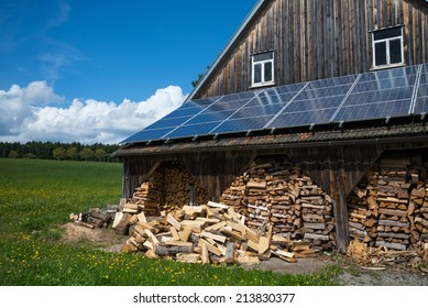 solar power panels on barn roof with stacked fire wood in front