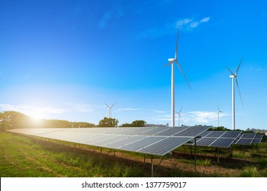 solar power panels with wind turbines against mountanis landscape against blue sky with clouds background,Alternative renewable energy concept.