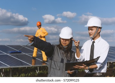 Solar power plant. Engineer and worker work in solar power plant  on a background of photovoltaic panels with construction plan