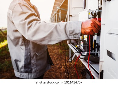 solar power plant to innovation of green energy; engineer or electrician working on checking and maintenance equipment at solar power plant