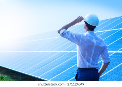 Solar power plant. Man standing near solar panels. Renewable energy.