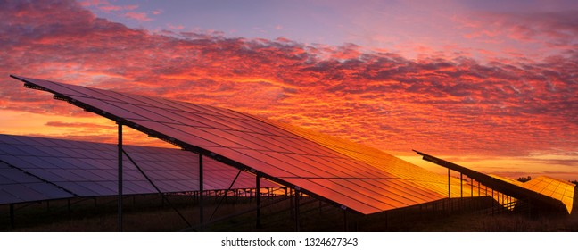 solar power plant on the background of dramatic, fiery sky at sunset