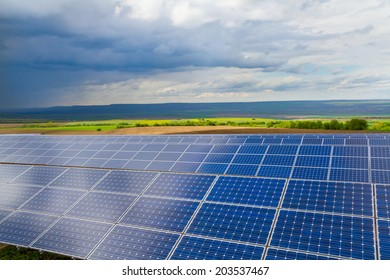 Solar power plant on the background of green fields and hills
