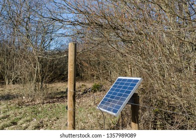 Solar power system by a fence in a rural landscape