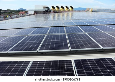 Solar PV System on Industry Roof with Cooling Towers Background