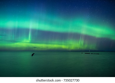 A solar storm developed during the blue hour leaving the aurora visible in a deep blue sky. Some reflections can be seen in Lake Superior.