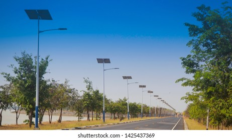 solar street light lamp post led with panel system on the road with blue sky and gree tree for background energy saving concept, landscaping shot photo.
