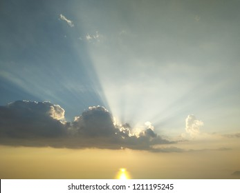 solar sunset with strong sunrays beyond the clouds, view from the mountains of the apuan alps in tuscany, near the versilia