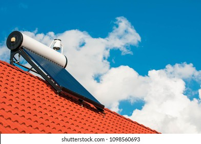 Solar water heater on rooftop, beautiful summer blue sky in the background.