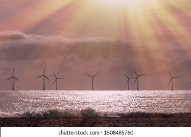 Solar wind and wave power. Beautiful alternative energy landscape scene. Sustainable resources calm and spiritual background image with offshore windfarm turbines and crepuscular sun rays at sunrise.
