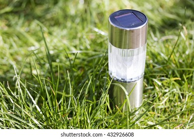 A solar-powered lamp illuminates a grass plant in garden