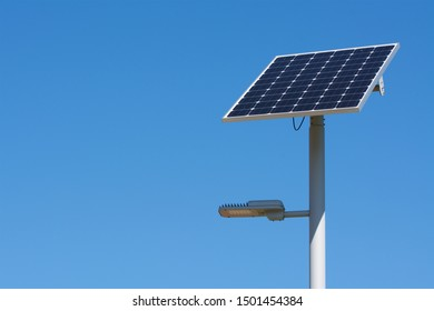 A solar-powered street lamp on a bright sunny day with blue sky and copy space on the left.