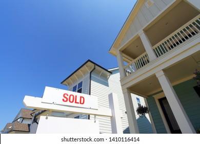 SOLD house sign at suburban neighborhood street