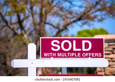 SOLD With Multiple Offers real estate sign near purchased house indicates red hot seller's market in the desired residential neighborhood. Blurred outdoor background.
