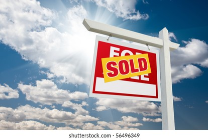 Sold For Sale Real Estate Sign over Clouds and Blue Sky with Sun Rays.