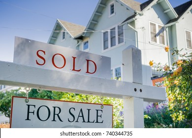 Sold sign in front of a house in a residential neighborhood, California