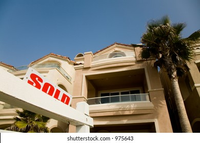 Sold sign in front of the luxury house in the suburbs.