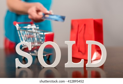 Sold sign with a shopping trolley and a bag