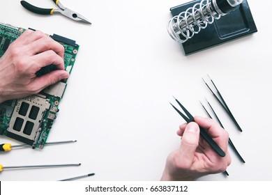 Soldering computer components flat lay. Top view on repairman hands fixing broken part in laptop motherboard. Electronics repair, construction, business concept