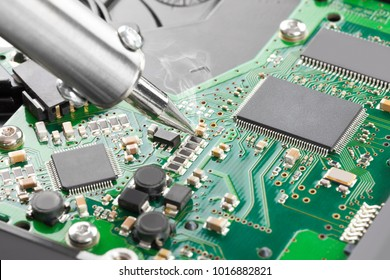 Soldering iron and green microcircuit - close up studio shot